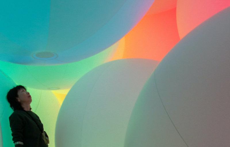 Frau steht zwischen aufblasbaren Latexballons
