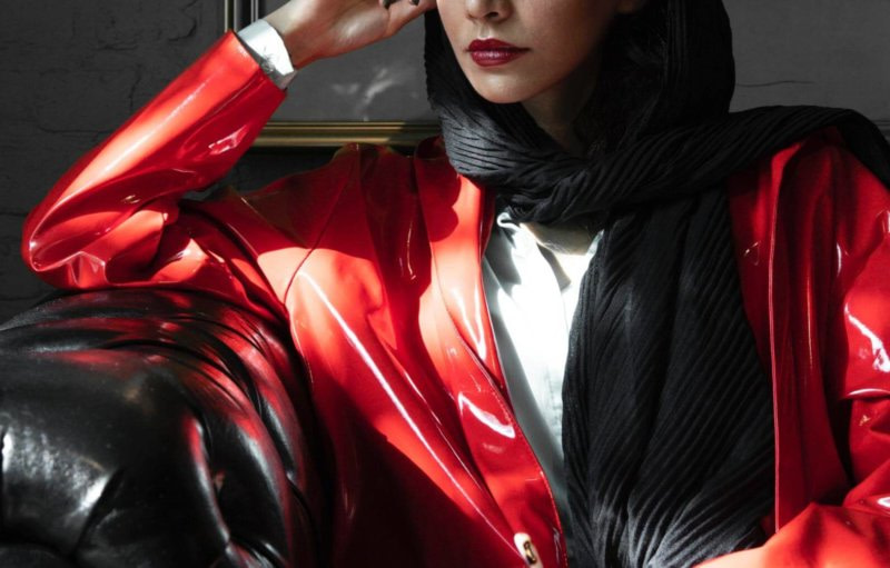 Frau in roter Latexjacke sitzt auf schwarzem Ledersofa