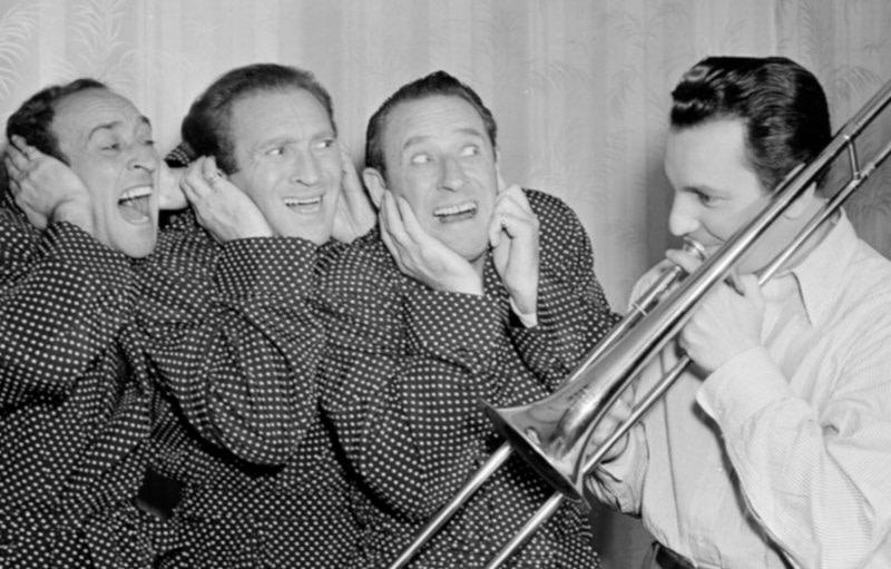 3 Männer halten sich die Ohren zu vor dem Mann mit der Trompete