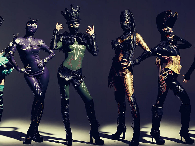 Mehrere Models in einer Reihe mit extravaganten Latex-Outfits
