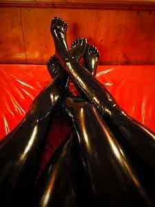 4 Beine in schwarzem Latex auf rotem Gummilaken
